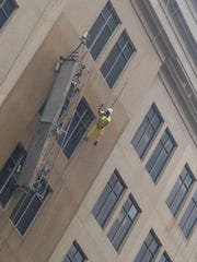 A man was dangling from the building for about 15 minutes this morning in Wilmington.