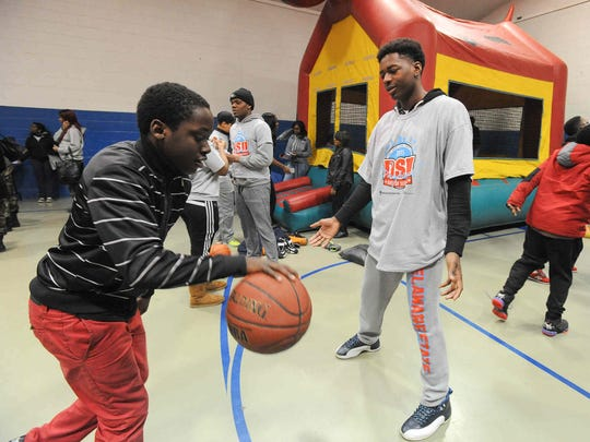Delaware State University freshman Dwayne Thomas (right) works with Dimarcus Williams, 15, of Dover, on his basketball game at the Greater Boys and Girls Club in Dover.