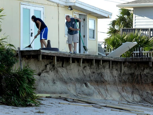 Rob Jakoby and his son Jake sweep debris off the eroded deck at his damaged beach home at Ponte Vedra Beach, Fla., Saturday, Oct. 8, 2016, after Hurricane Matthew passed through Friday.