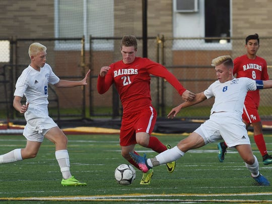 Red Hook's Hayden Campalong, center, attempts to move the ball against Goshen during the Section 9 Class A boys soccer final last October.