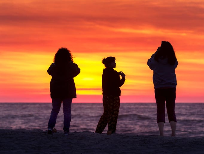 Jackie Hangley and Grace Hangley of Hopatcong, NJ, watch the sunrise with Lara Hangley of Toughkenamon, Pa, on the beach in Ship Bottom. Sunrise in Ship Bottom on Long Beach Island on June 22, 2013.   Photo by Peter Ackerman