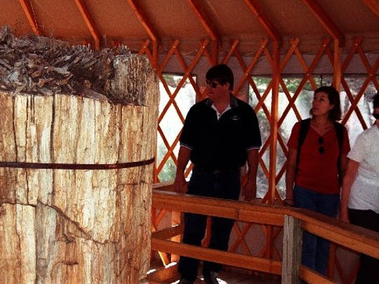 Visitors at Florissant Fossil Beds National Monument check out one of the covered petrified redwood stumps.The yurt-like cover protects the exposed stump from the elements.