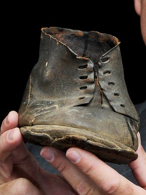 """Shawn Henry of Nashville hold his Civil War treasure: his ancestor's half boot. The ancestor had his foot shot in the Civil War and had a Union cobbler specially make a customized half boot. It is one of the most amazing items that the state's """"Looking Back"""" project has turned up while touring the state for artifacts."""