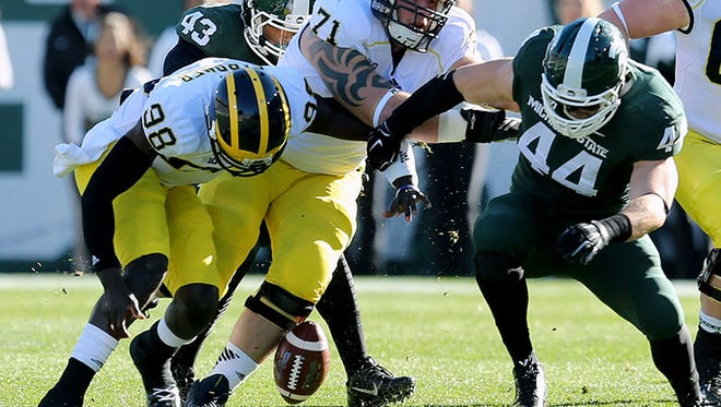 Michigan QB Devin Gardner and Michigan State LB Marcus Rush go after the ball during Saturday's game in East Lansing.