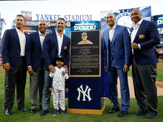 Derek Jeter stands next to his Monument Park plaque