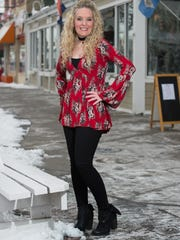 Allison Griffith Sullivan wears a Free People printed bell-sleeve top, Gap black denim jeans with zip detail and black SBICCA fold-over vegan booties.