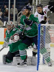 Atlanta Gladiators forward Phil Lane (29) stakes out the backdoor with Florida's Gus Young (2) helping Everblades' goalie Callum Booth defend the net during  a first-round playoff game at Infinite Energy Arena in Duluth, Ga., on Thursday, April 19, 2018.