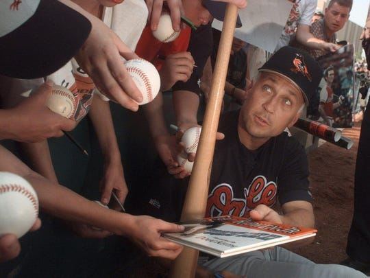 In this June 1999 photo, Baltimore Orioles infielder Cal Ripken, right, is surrounded by fans asking for autographs before the start of the exhibition game between the Orioles and the Red Wings.