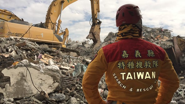 A member of rescue teams stands by as heavy excavation