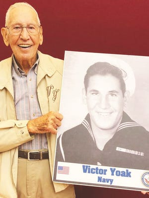Vic Yoak poses with his Navy photograph that is carried on a poster in each Ripley Veterans Day Parade.