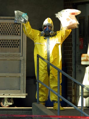 An investigator wearing a hazardous materials suit emerges from a post office in October 2001 in West Trenton, N.J., during an investigation into the mailing of letters containing anthrax.