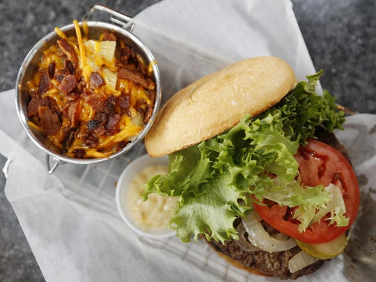 A side of bacon-topped mac and cheese sits alongside The Barnstormer at Guttenburgers in West Des Moines. The burger features two beef patties with lettuce, tomatoes and grilled onions with a side of horseradish sauce.