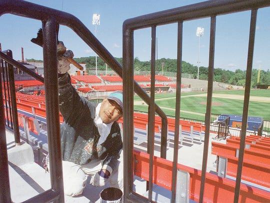 Arturo Montes paints a railing at Yogi Berra Stadium