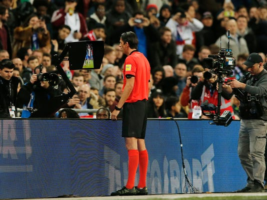 Referee Deniz Aytekin checks the VAR during the international friendly soccer match between England and Italy at the Wembley Stadium in London, Tuesday, March 27, 2018. (AP Photo/Alastair Grant)