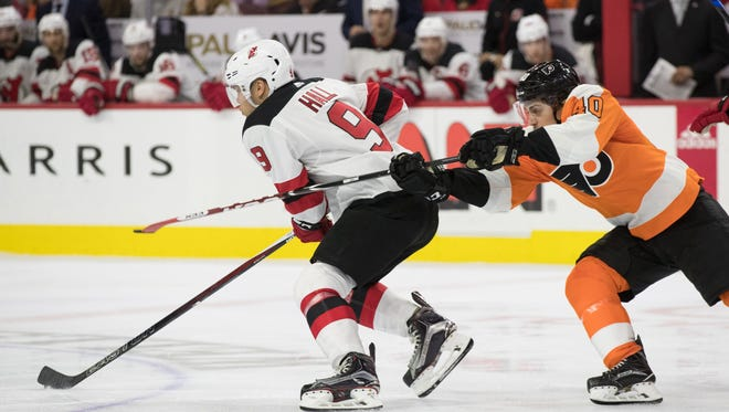 New Jersey Devils left wing Taylor Hall (9) skates past the check of Philadelphia Flyers center Jordan Weal (40) during the second period at Wells Fargo Center.