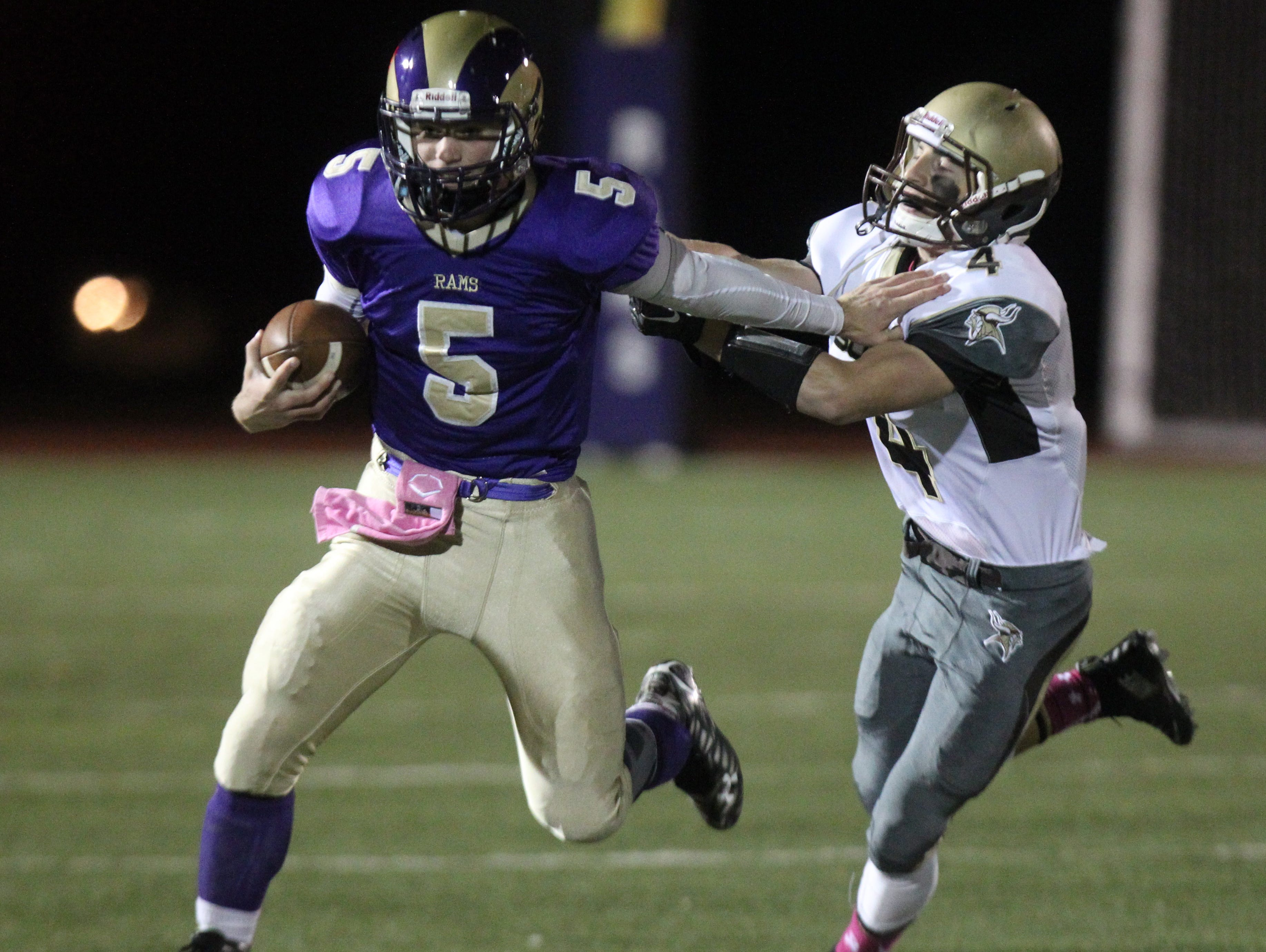 Clarkstown North's Jack Abrams straight-arms Clarkstown South's Kyle Samuels during their Class AA quarterfinal at Clarkstown North Oct. 23, 2015.