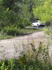 A car on Heineberg Drive/Vermont 127 in Colchester drives past a partially paved state right-of-way, originally planed as the western terminus for the now-abandoned Circumferential Highway. Photographed on Thursday, September 1, 2016.