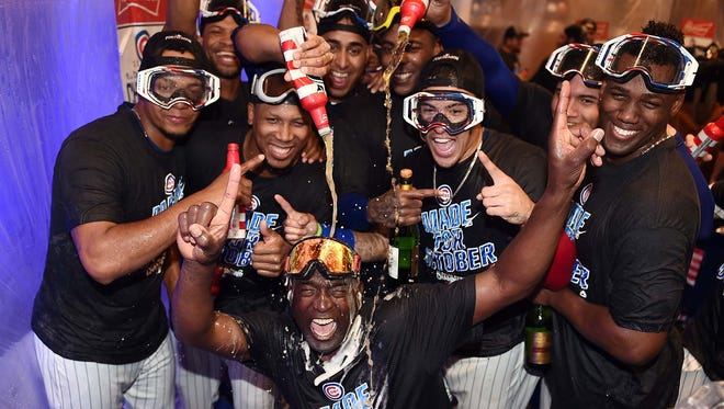 Members of the Chicago Cubs celebrate in the locker room following a victory over the Milwaukee Brewers at Wrigley Field on September 16, 2016 in Chicago, Illinois.  The Cubs clinched the NL Central Division.