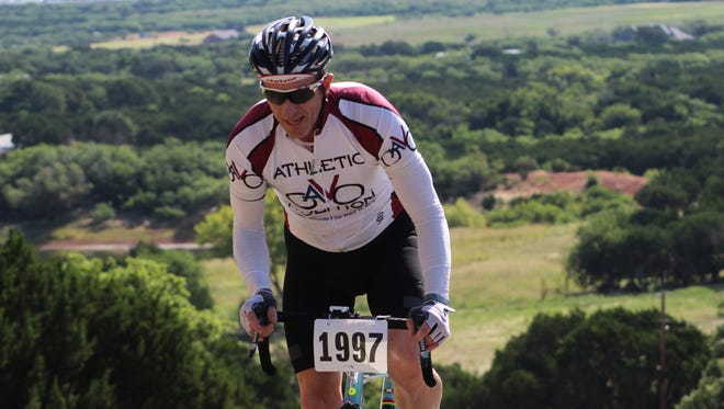 Chris Gescheidle, of Richardson, stands up for his ascent up Steamboat Mountain near the finish of Sunday's time trial. He was sixth overall in a time of 23 minutes, 18 seconds.