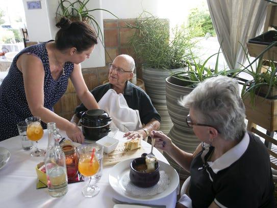 Ségolène Gros serves a dish to patrons, Richard and