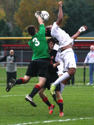 Livonia Churchill goal-keeper Nathan Guzowski (3) and teammate Conner Rash converge to prevent Plymouth's Jayden Huxtable from connecting on a header during Wednesday night's match.