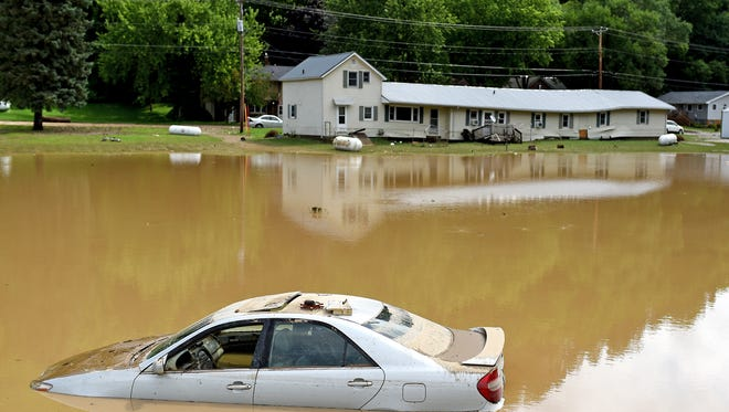 A car is submerged due to flood water near the bridge over Brewery Creek following Friday night storms in Cassville, Wis., on Saturday, July 22, 2017.