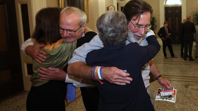 Richard Martinez, right, whose son Christopher Ross Michaels-Martinez was killed in a shooting spree in Isle Vista, hugs State Sen. Hannah-Beth Jackson, D-Santa Barbara, after the bill she carried, that will allow courts to temporarily remove firearms from people who show signs that they could harm themselves or others, was approved by the Senate in Sacramento, Calif., Wednesday, Aug. 27, 2014.  The bill, AB1014, approved by a 23 will allow law enforcement and immediate family members to seek are restraining order removing fire arms for 21 days. At left Assemblywoman Nancy Skinner, D-Berkeley, is hugged by Bob Weiss, whose daughter, Veronika, was also killed last May in the mass shooting near the University of California, Santa Barbara.  Skinner, and Jackson, along with Assemblyman Das Williams, D-Santa Barbara, were co-authors of the bill. (AP Photo/Rich Pedroncelli)