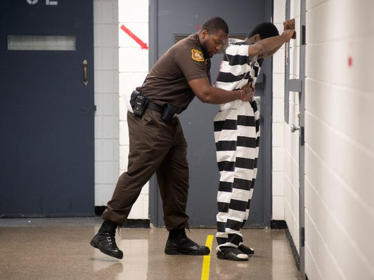 Corrections Officer Terence Moore frisks an inmate July 18 before the inmate meets with his attorney at the Saginaw (Mich.) County Jail.