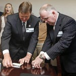 Rep. Bo Eaton, D-Taylorsville, left, a 20-year incumbent, and Republican challenger Mark Tullos, right, open business card boxes Friday in Jackson. Eaton picked the one with the longer straw, giving him the victory and blocking the GOP from having a super­majority.