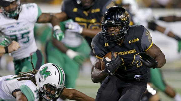 Southern Miss Golden Eagles running back George Payne (24) runs with the football defended by Marshall Thundering Herd safety Kendall Gant (14) in the second half at M.M. Roberts Stadium. Southern Miss won 24-14. Mandatory Credit: Chuck Cook-USA TODAY Sports