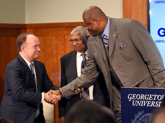 Georgetown's new men's basketball head coach Patrick Ewing, right, shakes hands with Georgetown University president John J. DeGioia, left, during an NCAA college basketball press conference, Wednesday, April 5, 2017, in Washington. Athletic director Lee Reed, center, watches.