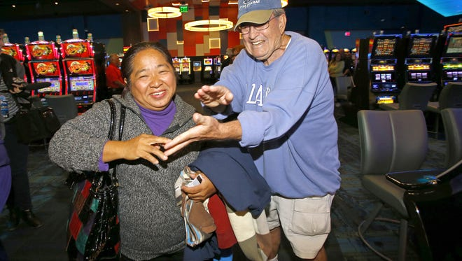 Resie Baeciong is congratulated by Dick Bridges on being the first person in the new Desert Diamond West Valley Casino Sunday, Dec. 20, 2015 near Glendale, Ariz.  Baeciong waited 24 hours spending the night in her car.