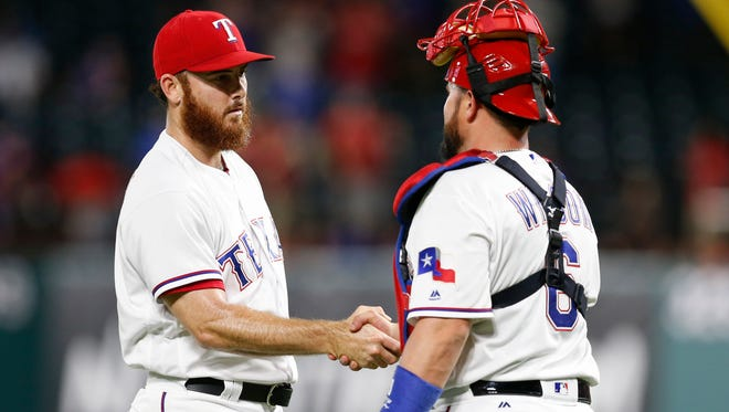 Texas Rangers relief pitcher Sam Dyson (47) and catcher Bobby Wilson (6) congratulate each other following their win over the Baltimore Orioles during a baseball game at Globe Life Park in Arlington. The Rangers won 4-3.
