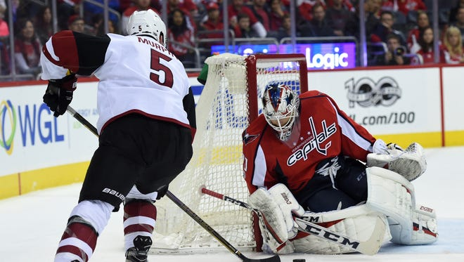 Washington Capitals goalie Braden Holtby (70) makes a save in front of Arizona Coyotes defenseman Connor Murphy (5) during the second period of an NHL hockey game Saturday, March 25, 2017, in Washington.