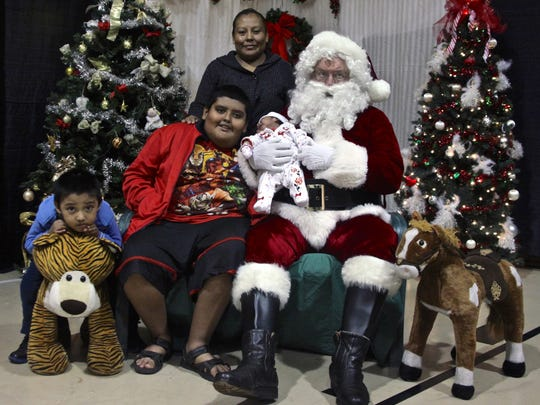 Mecca resident Reyna Perez and her three children pose for a photograph with Santa Claus during an event at Las Palmas Community Church in Indio on Dec. 17, 2015. The Coachella Valley Christmas store provided clothes, toys and meals to underprivileged families across the valley.