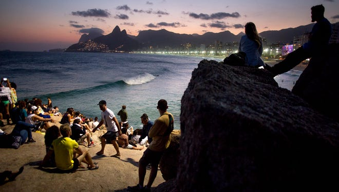 People watch the sunset at Pedra do Arpoador in Rio de Janeiro on Thursday, August 4, 2016.