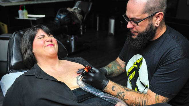 Breast cancer survivor Nat Crandall reacts as tattoo artist Jeff Barnard touches up the shading of her breast at Golden Yeti, his studio in Franklin. Barnard offers the service, which would typically cost $600-$1,000, to breast cancer survivors free of charge.