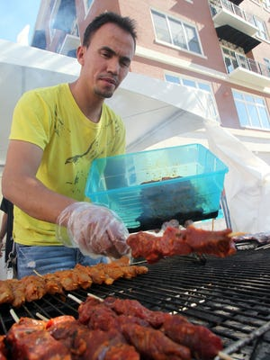 Hamid Karam of Des Moines loads beef kabobs onto his grill at the World Food Festival in the East Village.