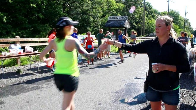 A runner is handed a water-filled paper cup as she passes through the Highland water station during last year's Walkway Marathon.