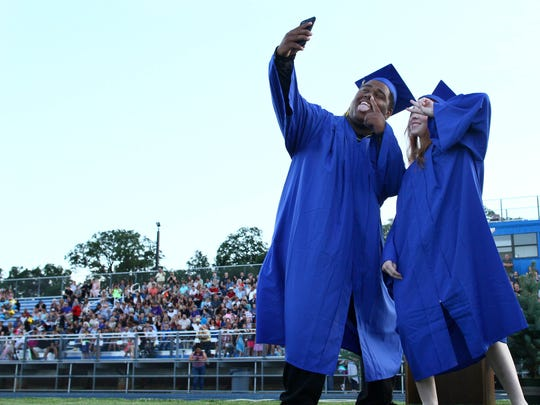 Devon Lammers, left, and Sophia Hill, take a selfie as they walk in Bob Reid Stadium for the commencement on Thursday night in Anderson.///Anderson Union High School, Class of 2017 Commencement on Thursday, June 1st, 2017, in Bob Reid Stadium. There are 112 graduates  receiving their diplomas on Thursday evening. /// (Photo for the Record Searchlight by Hung T. Vu)