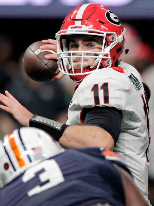 FILE - In this Dec. 2, 2017, file photo, Georgia quarterback Jake Fromm (11) passes as he is rushed by Auburn defensive lineman Marlon Davidson (3) during the Southeastern Conference championship at Mercedes-Benz Stadium, in Atlanta, Ga. One year after leading Georgia to the national championship game as a freshman starting quarterback, Jake Fromm can't relax. This spring's new competition at quarterback is Justin Fields, who is expected to push Fromm as the offense reloads after losing running backs Nick Chubb and Sony Michel.  (C.B. Schmelter/Chattanooga Times Free Press via AP, File)