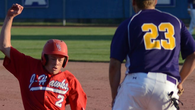 Johnston's first baseman Matt Shaver waits for the throw to first as Urbandale's Michael Englund slides back to first.