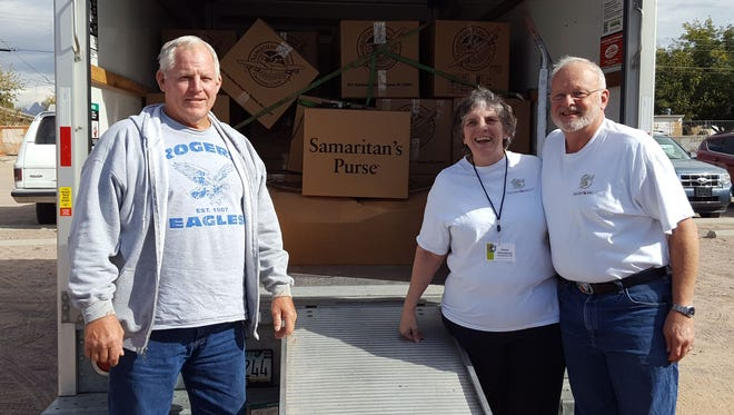 Pastor Joe Bryant, Stella and Loyd Dillenbeck from Grace Baptist Church of Alamogordo load a truck full of shoe box donations for transport to the Las Cruces Relay Center.