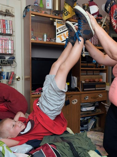 Tasha Burrage plays with her son, Bryson Hines, 5, after tying his shoes in his bedroom on Thursday,  July 19, 2018.  Burrage and her children are part of a pilot program with Youth Villages which is working with DCS to help prevent children from coming into foster care.