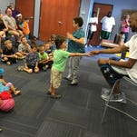 Portland native and Houston Rockets basketball player Corey Brewer takes a raffle ticket from fan Preston Murphy, 5, at the Portland Public Library on Friday.