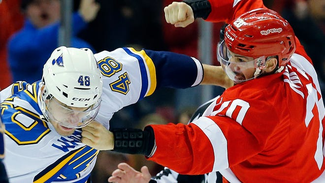 Detroit Red Wings left wing Drew Miller (20) fights St. Louis Blues defenseman Petteri Lindbohm (48) in the third period of an NHL hockey game in Detroit, Sunday, March 22, 2015.