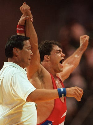 Kurt Angle of the United States celebrates his gold medal win over Iran's Abbas Jadidi in the 100 kg class of freestyle wrestling at the Centennial Olympic Games in Atlanta on July 31, 1996.