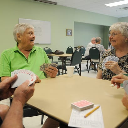 A group of people enjoy a card game among friends at the Whitney Senior Center in St. Cloud.