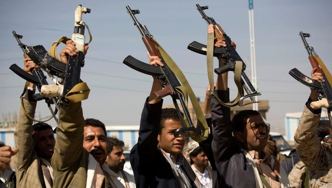 Houthi Shiite Yemeni raise their weapons during clashes near the presidential palace in Sanaa, Yemen, on Jan. 19, 2015.