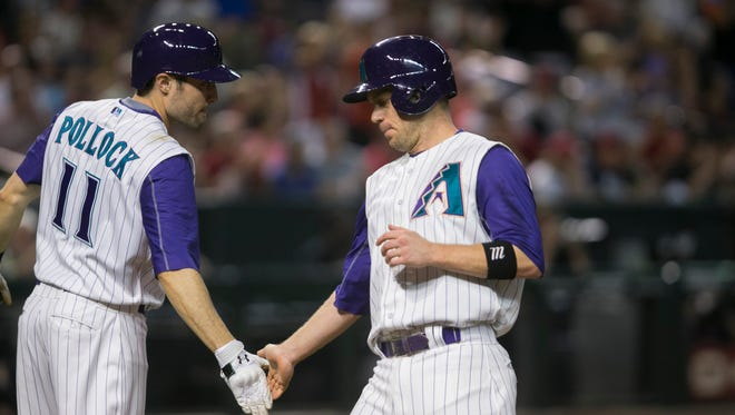 The Diamondbacks' A.J. Pollock congratulates Aaron Hill after Hill scored against the Cardinals in the second inning at Chase Field in Phoenix on Aug. 27, 2015.